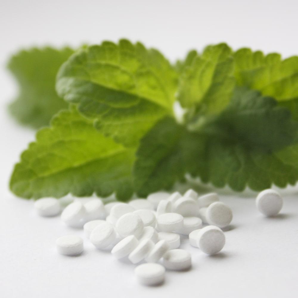 Stevia Süßstofftabletten und Stevia Blätter.